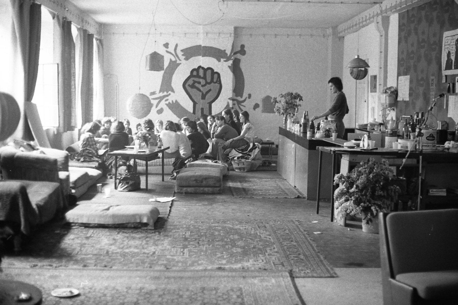 Schwarz-Weiß Fotografie des Gruppentreffen im LAZ, Kulmerstraße, Berlin-Schöneberg, 1975. Auf dem Foto ist eine Bar mit einer Person dahinter auf er rechten Bildseite zu sehen. Auf der linken Bildseite sitzt eine Gruppe von Personen zusammen. Auf der rückliegenden Wand ist eine übergroße, geballte Faus aufgemalt, die den Kreis sprengt, in dem sie sich befindet.