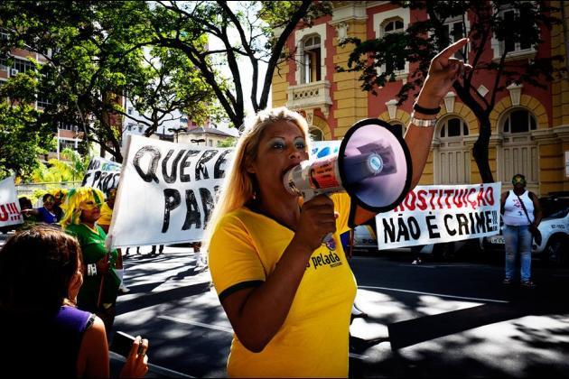 eine Person mit einem gelben T-Shirt und langen Haaren spricht auf einer Demo in ein Megafon