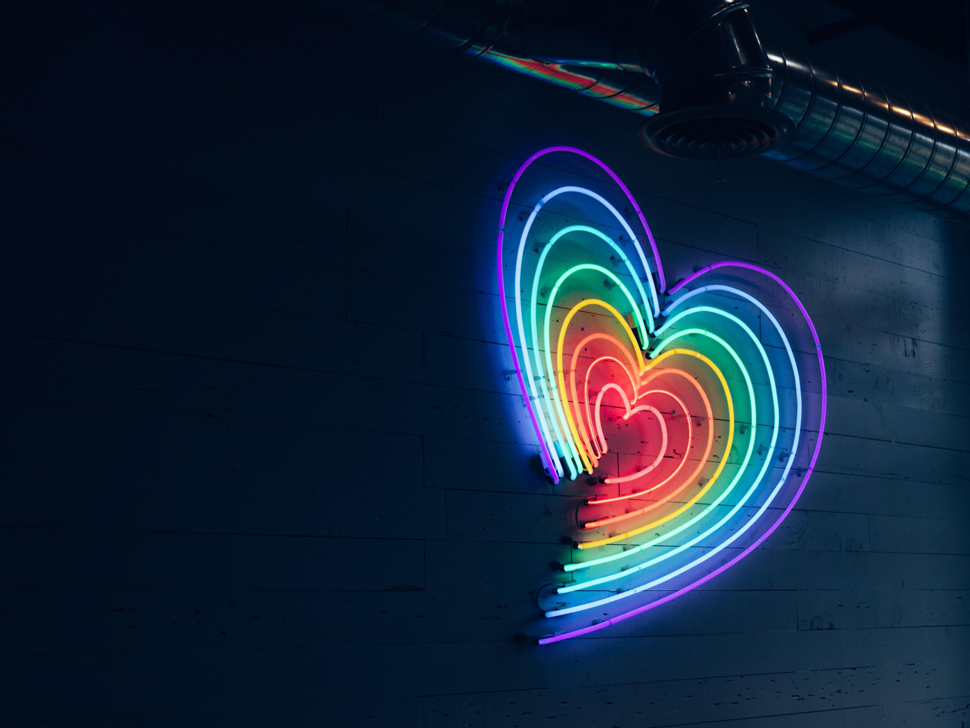 Ein Neonschild in Herzform mit Regenbogenfarben